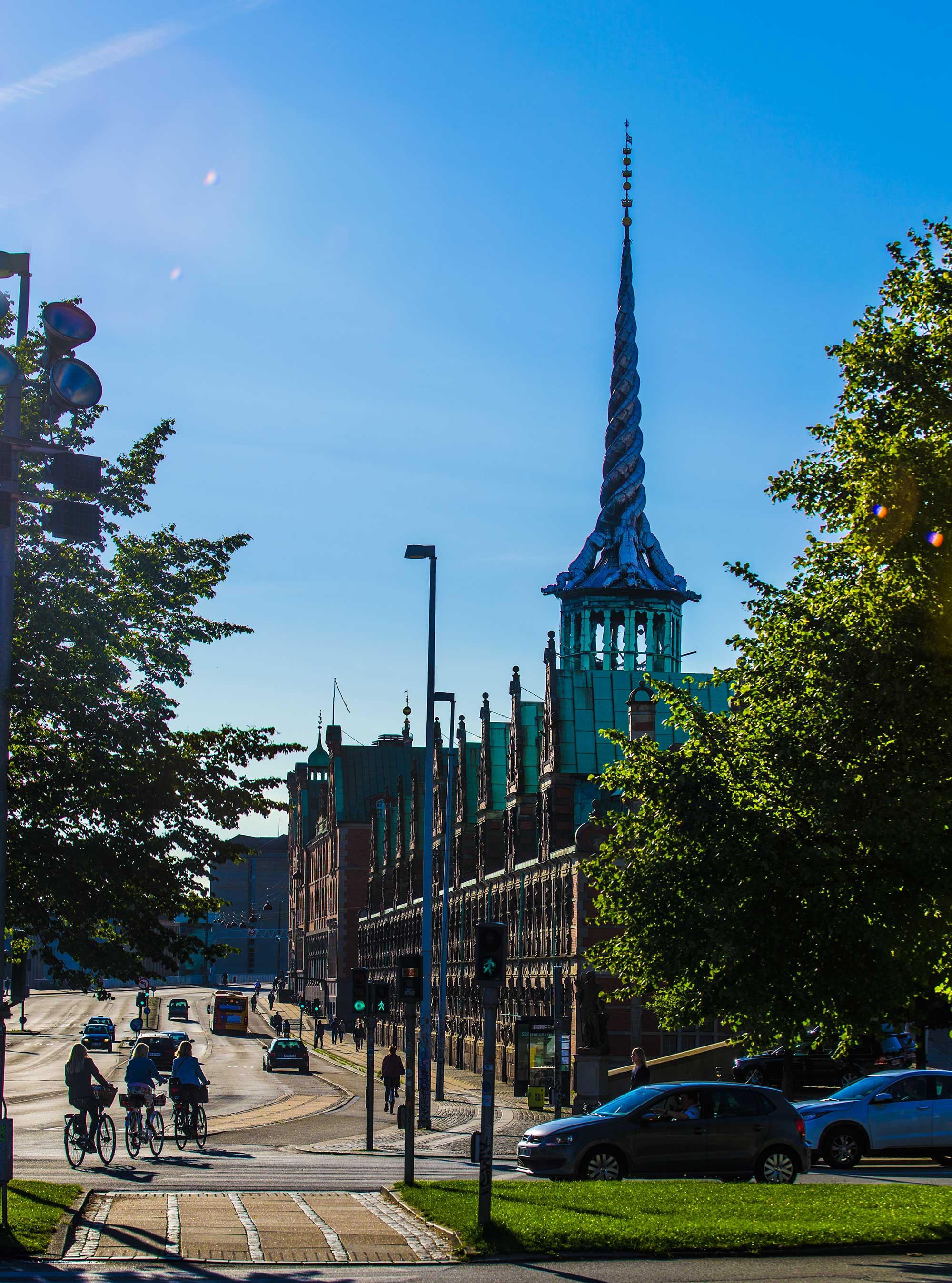 Børsen København Tårn i morgensol med cykelister i forgrund- Fotograf i Kbh - krestenhillerup.dk